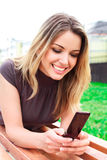 Laughing young woman reads sms. Laying on a bench in a park Royalty Free Stock Photography