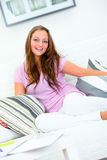Laughing young woman relaxing on couch at home Royalty Free Stock Images
