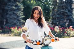 Laughing young woman on scooter Royalty Free Stock Photography