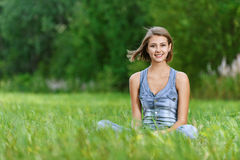 Laughing young woman sitting on Stock Photography