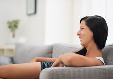 Laughing young woman sitting on couch in room Royalty Free Stock Image