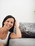 Laughing young woman sitting near sofa Royalty Free Stock Photo