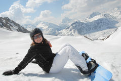 Laughing young woman sitting in snow with snowboar Stock Photos