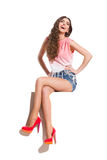 Laughing Young Woman Sitting On A Top Of Something. Laughing young woman in pink top, jeans shorts and red high heels sitting on the top of white banner. Full royalty free stock photography