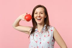 Laughing young woman in summer clothes holding fresh ripe red apple fruit isolated on pink pastel wall background stock photos