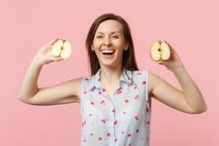 Laughing young woman in summer clothes holding in hands halfs of fresh ripe apple fruit isolated on pink pastel. Background in studio. People vivid lifestyle royalty free stock photography