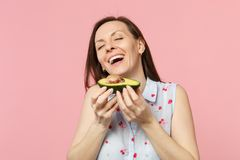 Laughing young woman in summer clothes keeping eyes closed holding fresh ripe green avocado fruit isolated on pink. Pastel background. People vivid lifestyle stock photo