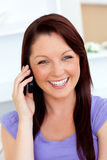 Laughing young woman talking on phone at home Stock Photography