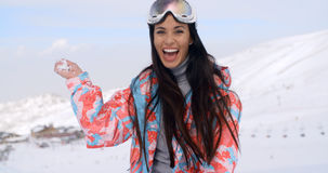 Laughing young woman throwing a snowball. Laughing vivacious attractive young woman standing in the snow on a mountainside throwing a snowball at the camera as Royalty Free Stock Images