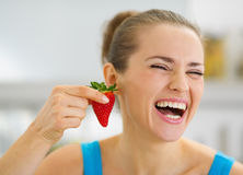 Laughing young woman using strawberry as earring Stock Photo