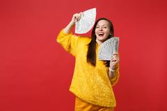 Laughing young woman in yellow fur sweater holding fan of money in dollar banknotes, cash money isolated on bright red. Wall background. People sincere emotions royalty free stock photo