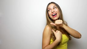 Laughing young woman in yellow tank top looking and pointing away with thumbs over white background.  stock photography