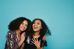 Laughing young women in stylish clothing. Standing over blue background in studio Stock Photography
