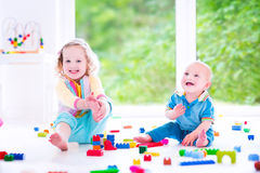 Laughings brother and sister playing with colorful block Stock Photography