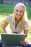 Laughiong young blond girl with laptop outdoors Royalty Free Stock Image