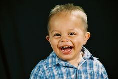 Laughter. Boy laughing with black background Royalty Free Stock Image