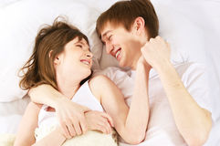 Laughter in bed. Young laughing couple in bed Royalty Free Stock Photo