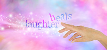 Laughter is the Best Medicine. Female hand pointing at a sparkly glittering `LAUGHTER HEALS` on a pink and blue bokeh background stock photography