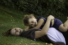 Laughter is the best medicine. Mom and Daughter time, spent rolling around on the grass laughing their butts off Royalty Free Stock Photo