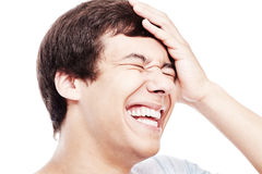 Laughter closeup. Close up of young hispanic man laughing out loud with closed eyes and hand on his head - laughter is best medicine concept Royalty Free Stock Photo