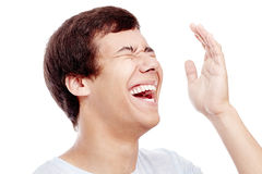 Laughter closeup. Close up of young hispanic man laughing out loud with closed eyes and hand near his head - laughter is best medicine concept stock photography