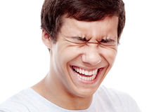 Laughter closeup. Face close up of young hispanic man laughing out loud with closed eyes - laughter is best medicine concept Stock Photos