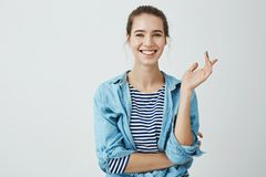 Laughter eases everyday problems. Charming woman in trendy outfit with bun hairstyle gesturing while talking to friend. Standing with crossed hand over body stock images