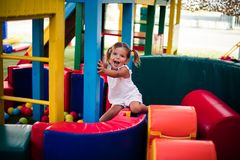 Laughter is important for a happy childhood. Smiling and happy little girl in playground Stock Photos