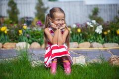 laughting美丽的女孩坐在她的庭院里和 免版税库存图片