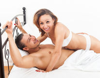Laughting adult couple having sex on bed in bedroom interior Stock Photo