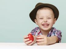Laughting-Junge 4 Jahre alt mit roten Ostereiern Stockfotos