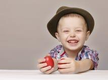 Laughting-Junge 4 Jahre alt mit roten Ostereiern Stockbilder