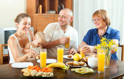 Laughting three generations family eating fresh friuts and vegit. Ables in the living room Royalty Free Stock Photography