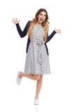 Laugjing Woman With Arms Outstretched Is Standing On One Leg. Beautiful young woman in white dotted summer dress and blue cardigan and sneakers is standing on royalty free stock images