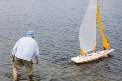 Launch boat 3. Radio controlled model sailboat on lake being launched  by senior citizen Royalty Free Stock Photography
