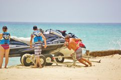 Launching jet ski on beach by professional staff Stock Images