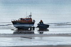 Launching lifeboat from beach at low tide. Royalty Free Stock Image