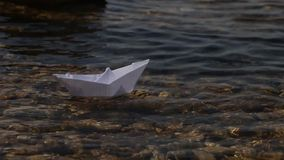 Launching a paper boat on a sunny day. Transparent water, current, path among obstacles. Launching a paper boat on a sunny day. Transparent water, current, path stock footage