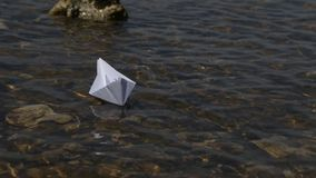 Launching a paper boat on a Sunny day. Transparent water, current, path among obstacles. Launching a paper boat on a Sunny day. Transparent water, current, path stock video footage