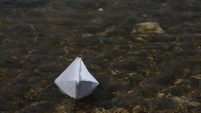 Launching a paper boat on a sunny day. Transparent water, current, path among obstacles.  stock video footage