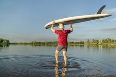 Launching stand up paddleboard Stock Photo