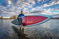 Launching stand up paddleboard on lake Royalty Free Stock Photography