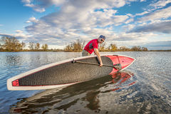 Launching stand up paddleboard on lake. Senior male launching his 14 feet long expedition stand up paddleboard on a lake in Colorado, fall scenery Stock Photography