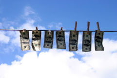 Laundered money #2. Seven Hundred Dollars in Laundered Money hanging on a clothes line drying in the sun on a beautiful blue sky day with white fluffy clouds