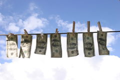 Laundered Money. $400.00 dollars (in $100.00 dollar bills) Dries on a laundry line in a beautiful spring day, with a blue sky back ground and white fluffy clouds stock photography