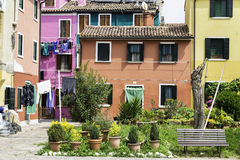 Laundries drying in the middle of the courtyard between traditional colorful houses in Burano Royalty Free Stock Image