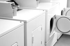 Laundromat. A row of coin operated washer and dryer machines Stock Photo