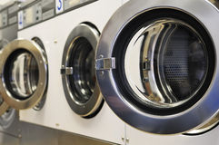 Laundromat. A row of industrial washing machines in a public laundromat stock photo