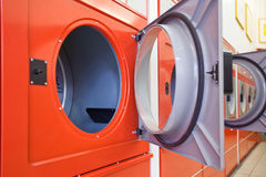 Laundromat. Empty open clothes dryers in a row at public laundromat royalty free stock image