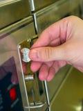 Laundromat feeding quarters. A hand feeding U.S. quarters into a washing machine at a laundromat Stock Photos